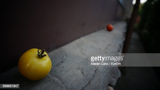 Close-Up Of Yellow Tomato On Retaining Wall