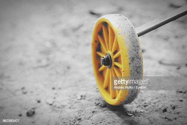 Close-Up Of Yellow Toy Wheel On Street