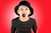 closeup of young boy in black shirt and black hat with heavy screaming expression and eyes wide open with crazy look on red background