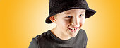closeup of young boy in black shirt and black hat with merry smiling expression