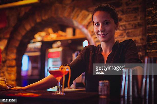 Close-up of young female bartender serving cocktail in cocktail bar