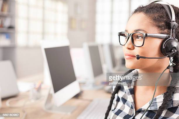 Close-up of young female call center operator with headphones