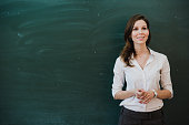 Closeup of young female teacher against chalkboard in class.