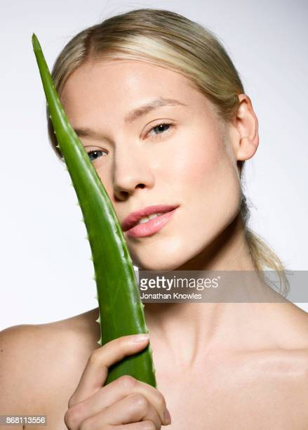 Close-up of young female with blond hair holding aloe
