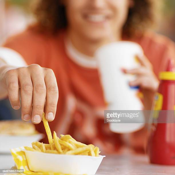 Close-up of young man eating in fast food restaurant