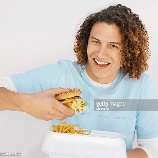Close-up of young man holding carton of French fries and eating burger