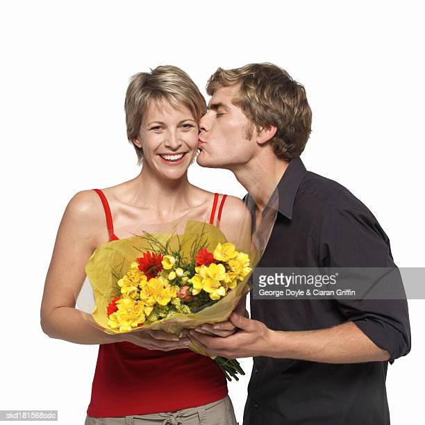 Close-up of young man kissing young woman and holding bouquet of flowers