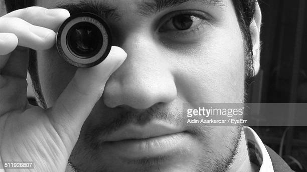 Close-up of young man looking through lens
