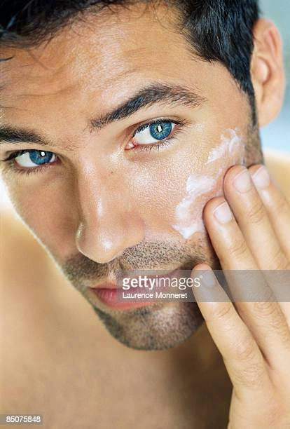 Closeup of young man putting cream on his cheek