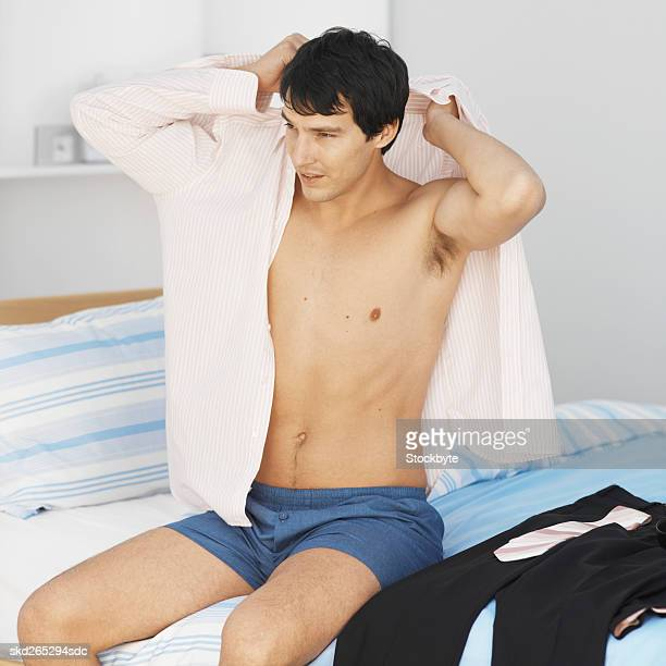 Close-up of young man putting shirt on while sitting on bed