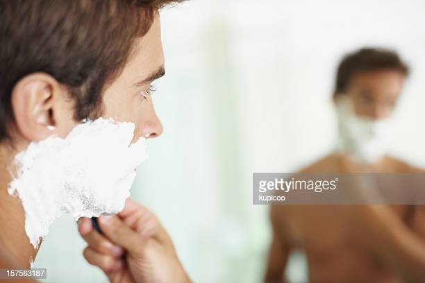 Closeup of young man shaving