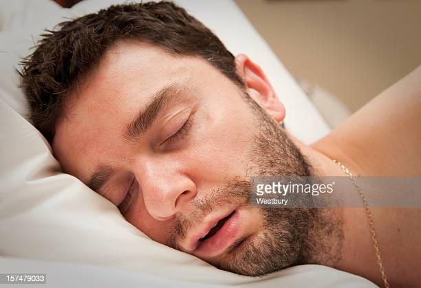 Close-up of young man with beard in sound sleep in bed