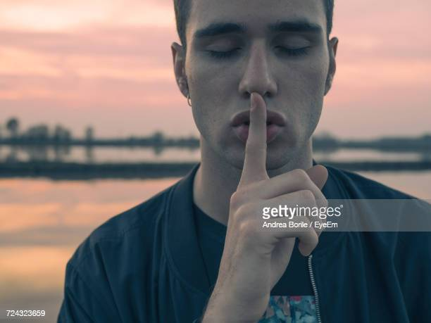 Close-Up Of Young Man With Finger On Lips By Lake During Sunset
