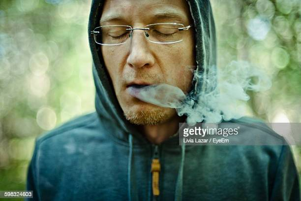 Close-Up Of Young Man With Hooded Shirt Smoking Outdoors