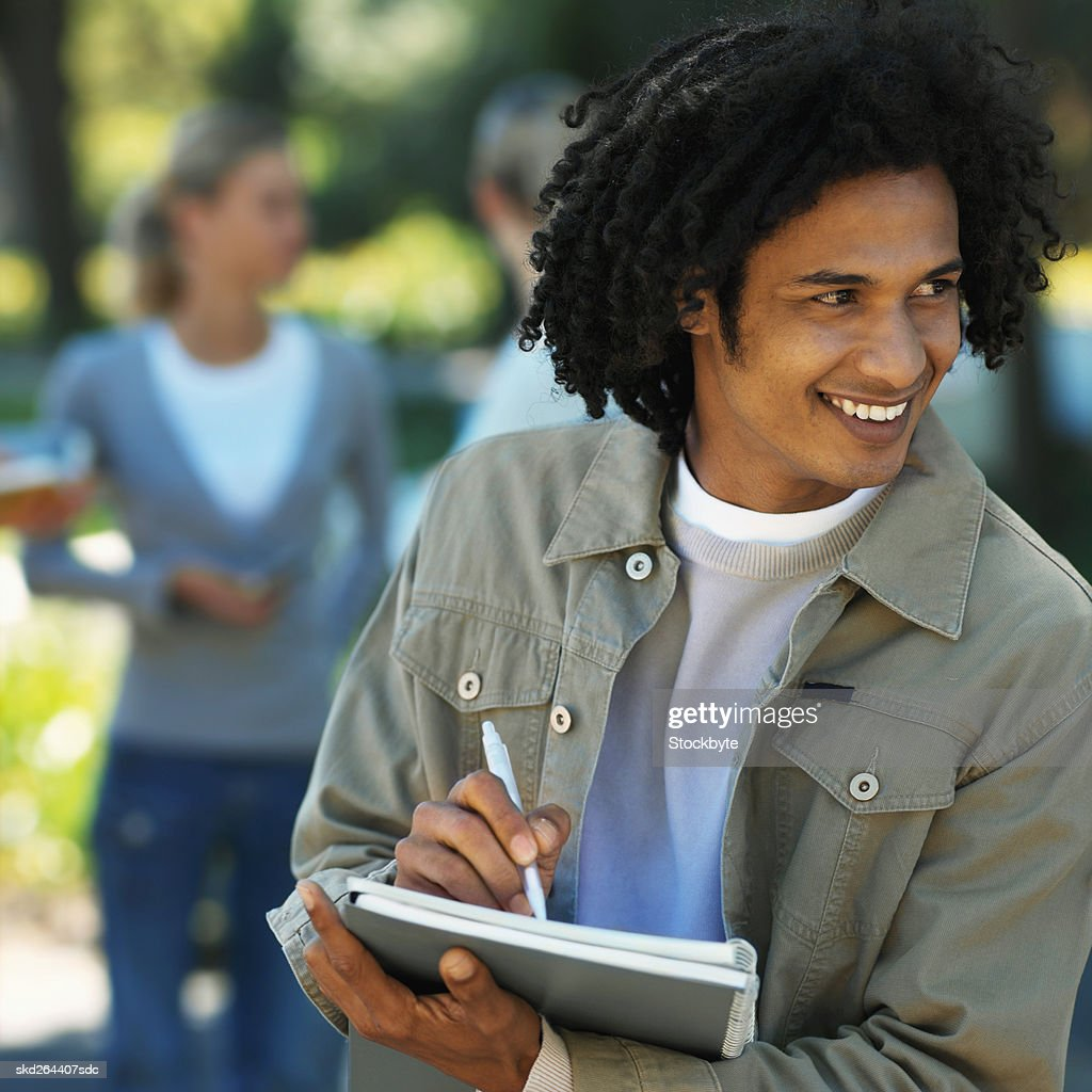 Close-up of young man writing on notebook with two other people in background : Stock Photo