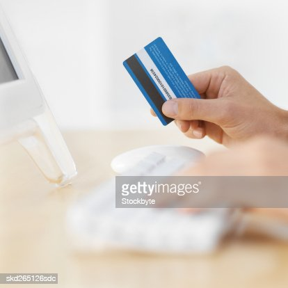 Close-up of young man's hands typing on computer keyboard and holding credit card : Stock Photo