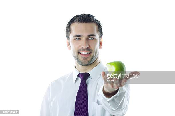 Close-up of  young smiling businessman holding bitten apple