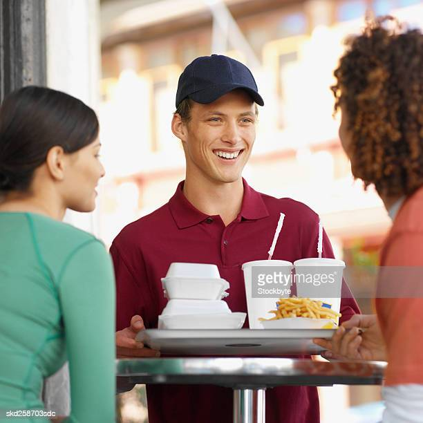 Close-up of young waiter giving fast food tray to young couple