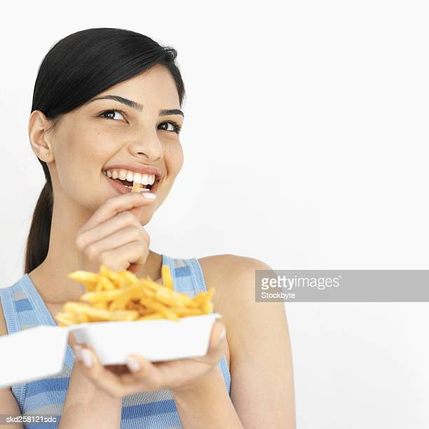 Close-up of young woman eating carton of French fries