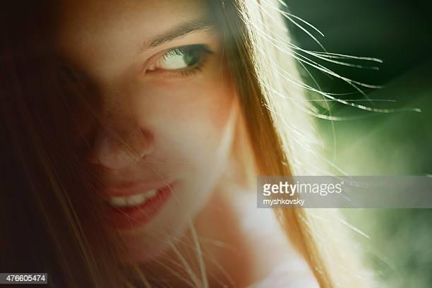 Gros plan visage de jeune femme dans la forêt.