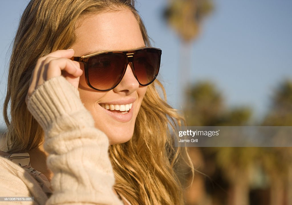 Close-up of young woman in sunglasses, smiling : Stock Photo