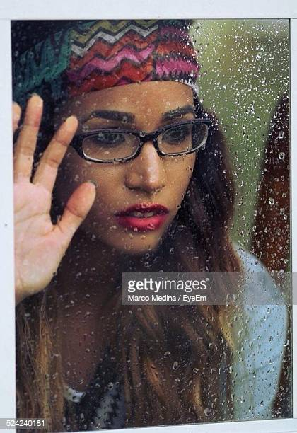 Close-Up of Young Woman Looking Towards Wet Window