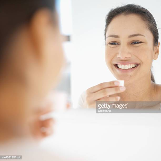 Close-up of young woman rinsing her mouth with mouthwash