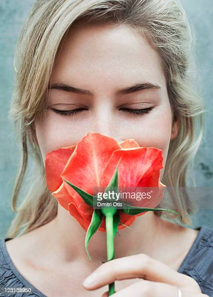 Close-up of young woman smelling red rose