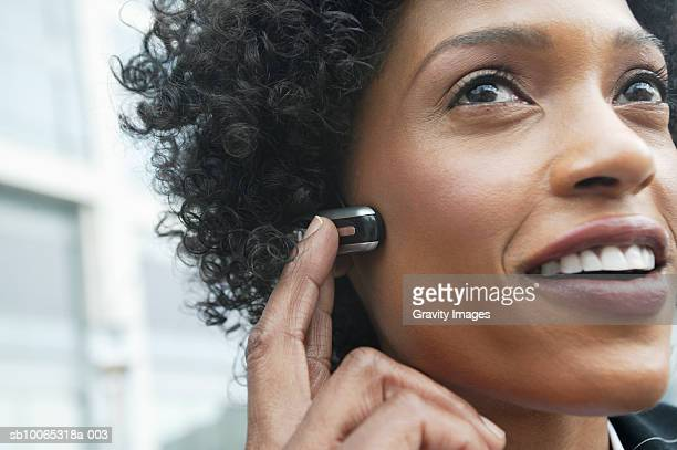 Close-up of young woman using headset