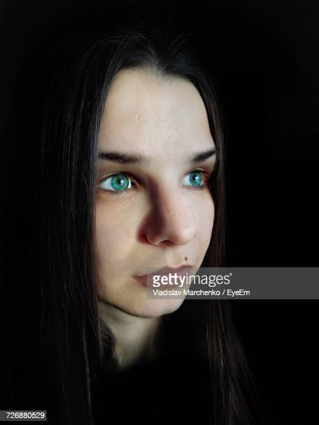 Close-Up Of Young Woman With Green Eyes Looking Away Against Black Background
