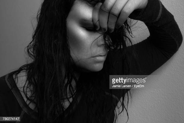 Close-Up Of Young Woman With Hand In Hair Against Wall