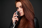 Closeup portrait of young woman with retro microphone
