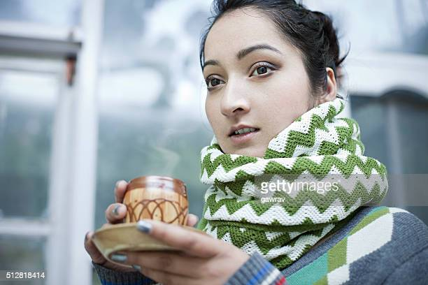 Close-up of young woman with steaming coffee mug in winter.