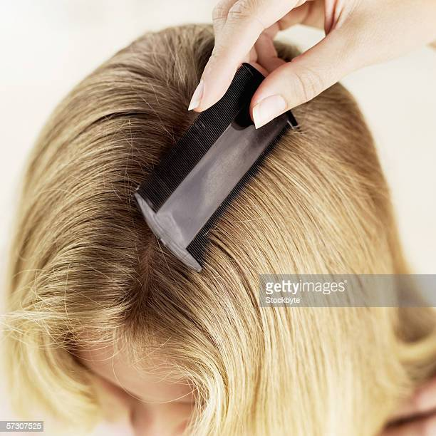 Close-up of young woman's hair being combed