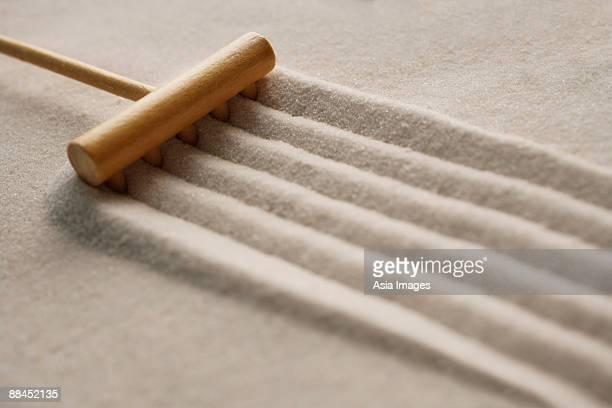 closeup of zen sand garden with rake