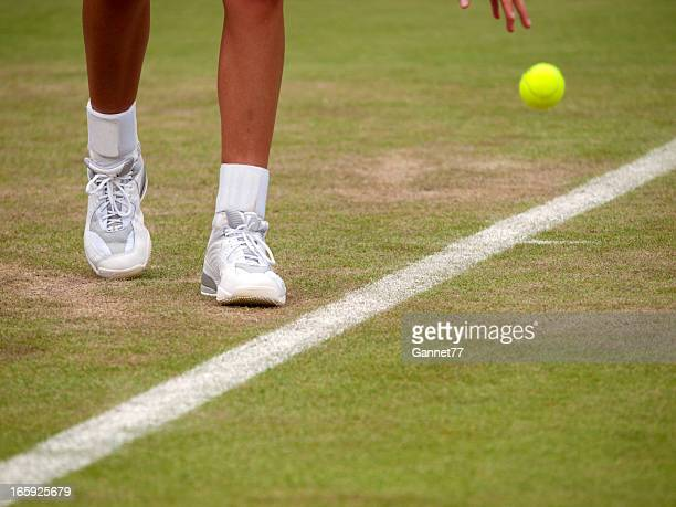 Close-up on a tennis player's feet as they prepare to serve