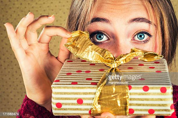 Close-up on eyes and hand opening a wrapped gift