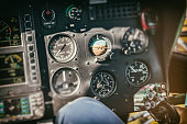 Close-up on different flight instruments in big helicopter air vehicle, taken from cockpit interior in flight. Control panel in selective focus and during a sunny summer day. All brands were removed.