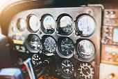 Vibrant color photography horizontal composition of close-up on several common flight instruments in old small propeller airplane cockpit interior without people in the frame, and selective focus on c