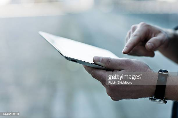 Closeup on mans hands holding Ipad.