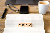 Closeup on notebook over desk background, focus on wooden blocks with letters making EOFY End of Financial Year text. Concept image. Laptop, glasses, pen and mobile phone in defocused background