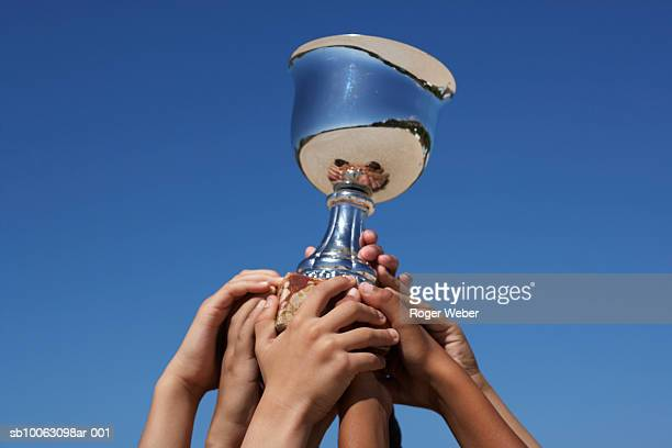 Close-up on raised hands holding trophy against blue sky
