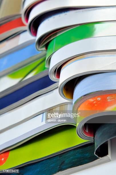 Close-up on stack of colourful open magazines