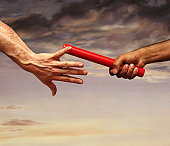 Close-up on the Hand of a Male Athlete Passing a Relay Baton to Another Athlete, With a Dramatic Sky in the Background