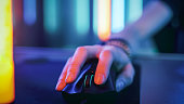 Close-up on the Hand that Uses Computer Mouse. Cool Neon Retro Lights. Browsing in Internet or Playing Online Games.