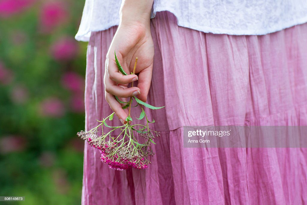 Closeup on woman's hand holding flowers by skirt