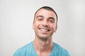 Closeup ortrait of smiling man in blue t-shirt. Positive facial emotion