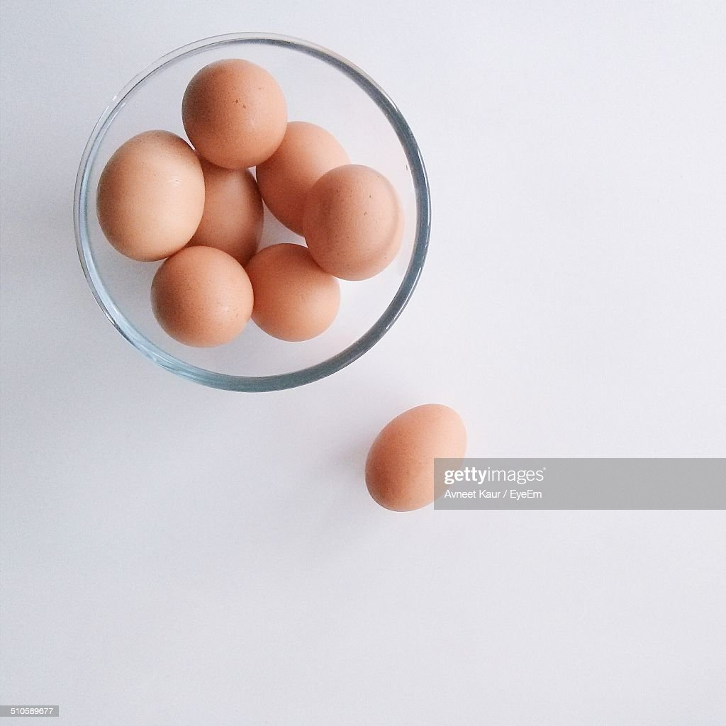 Close-up overhead view of eggs in bowl over white background