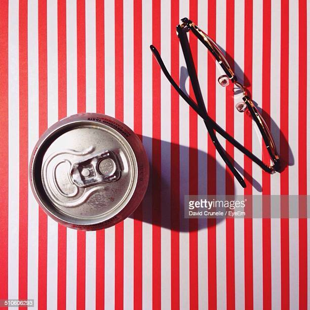 Close-up overhead view of tin can and glasses on striped table