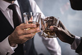 Close-up partial view of two men in formal wear clinking whiskey glasses